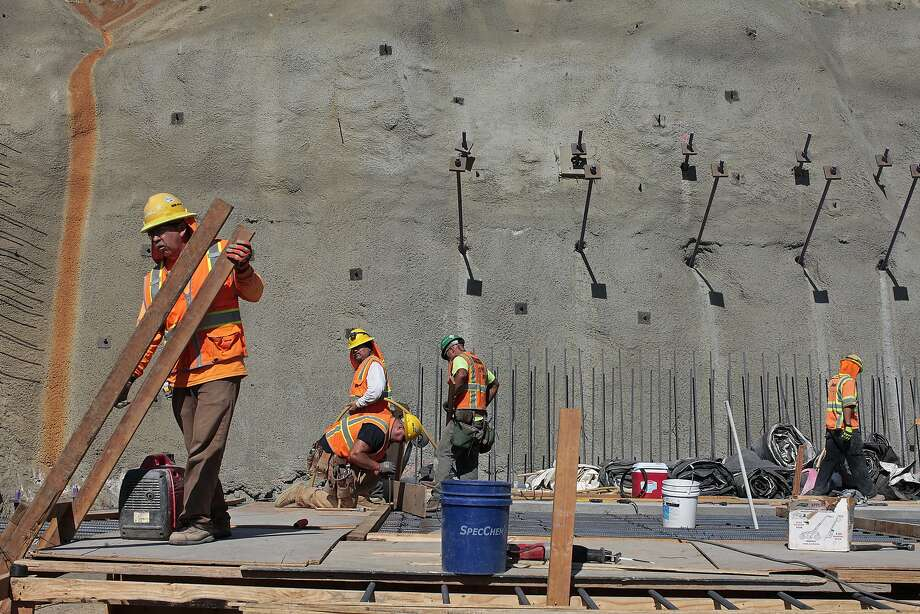 Construction crews work to build a spillway near the left abutment of the new Calaveras Dam near Fremont. The infrastructure project is part of a decade-old, $4.6 billion upgrade to the Hetch Hetchy water system. Photo: James Tensuan, The Chronicle