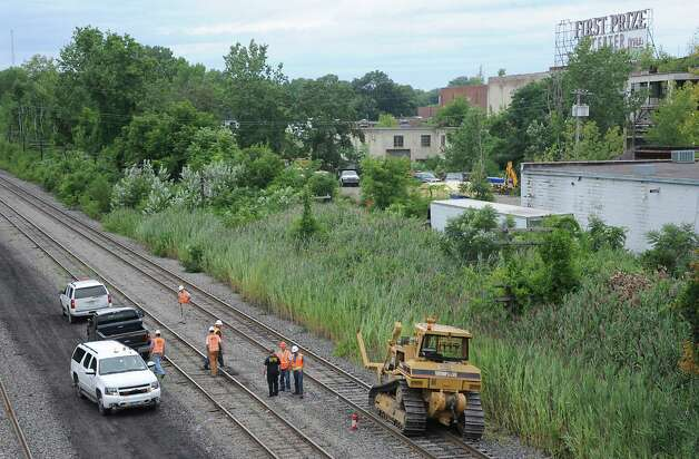 Workers from the Albany fire department and Amtrak stand next to a bulldozer which caught fire and then traveled along railroad tracks from Railroad Avenue to behind the First Prize Center in Colonie. The burning bulldozer caused damage to the tracks and is delaying passenger rail trips this evening Tuesday, Aug. 12, 2014 in Colonie, N.Y.  (Lori Van Buren / Times Union) Photo: Lori Van Buren