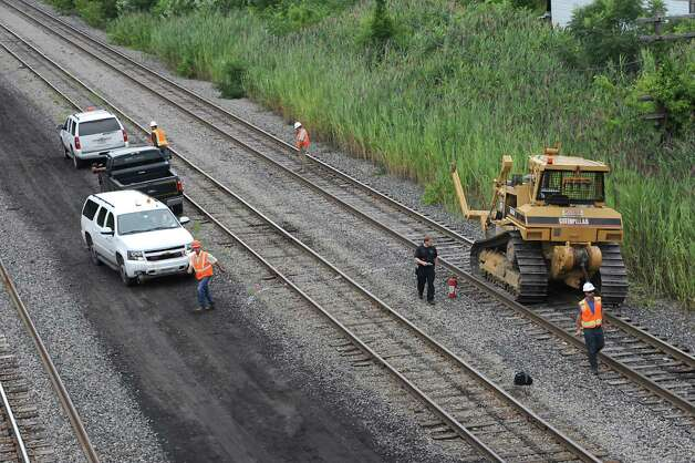 Workers from the Albany fire department and Amtrak are seen near a bulldozer which caught fire and then traveled along railroad tracks from Railroad Avenue to behind the First Prize Center in Colonie. The burning bulldozer caused damage to the tracks and is delaying passenger rail trips this evening Tuesday, Aug. 12, 2014 in Colonie, N.Y.  (Lori Van Buren / Times Union) Photo: Lori Van Buren