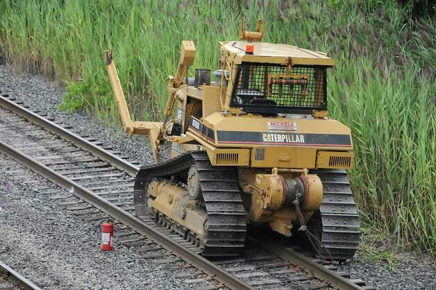 A bulldozer which caught fire and then traveled along railroad tracks from Railroad Avenue to behind the First Prize Center is seen still on the tracks. The burning bulldozer caused damage to the tracks and is delaying passenger rail trips this evening Tuesday, Aug. 12, 2014 in Colonie, N.Y.  (Lori Van Buren / Times Union) Photo: Lori Van Buren
