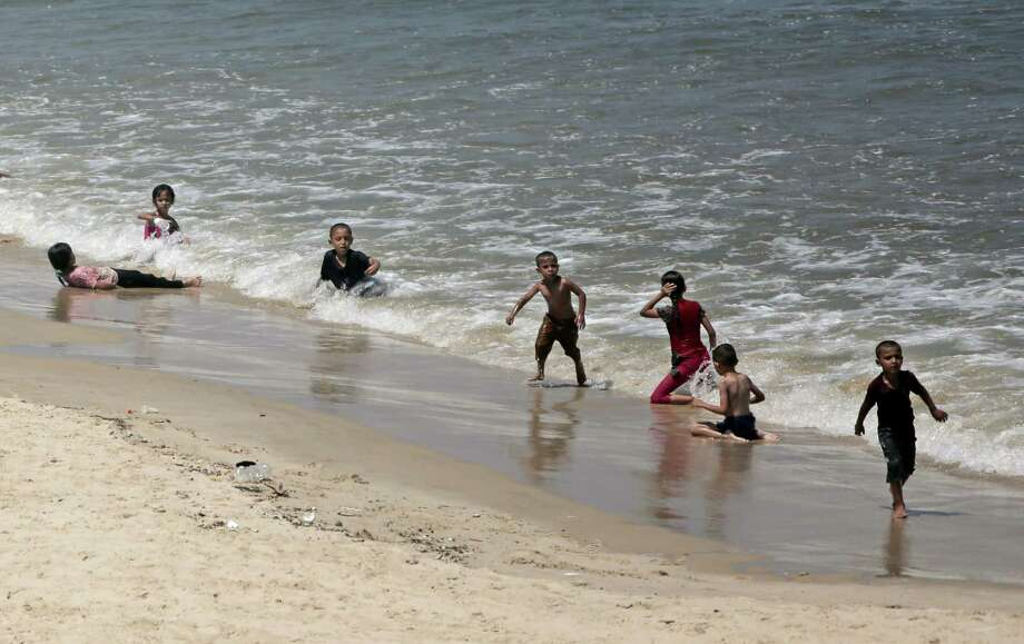 Palestinian children swim on the beach of Gaza City, Tuesday, Aug. 12, 2014.(AP Photo/Khalil Hamra) Photo: Khalil Hamra, STF / AP