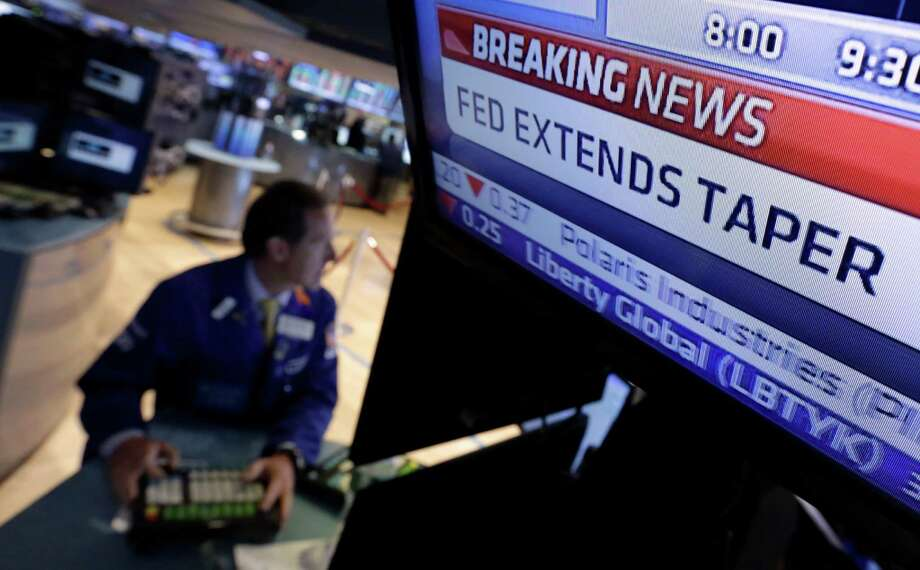 FILE - In this June 18, 2014 file photo, a television monitor at a trading post on the floor of the New York Stock Exchange shows the decision of the Federal Reserve. Like with other higher-risk investments, investors have pulled back from junk, or high yield, bonds because they worry about the end of the Federal Reserve's policy near-zero interest rates. Investors expect the central bank to raise rates sometime next year, and that means the value of bonds currently held in portfolios will fall.  (AP Photo/Richard Drew, File) Photo: Richard Drew, STF / AP