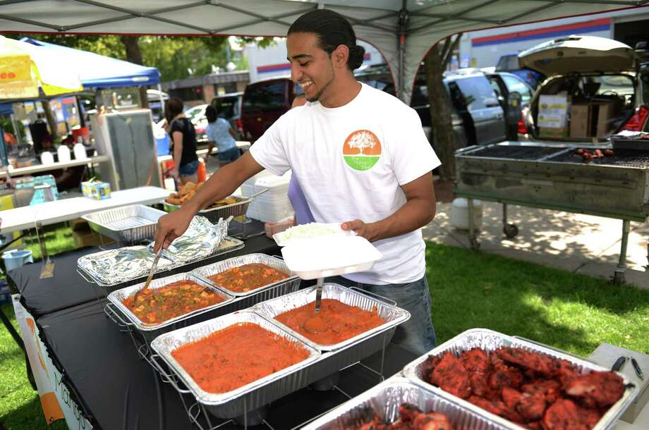 Sim Singh, of The Mango Tree Indian Takeout and Cuisine, serves an Indian dish at the Jai Ho Indian Festival at CityCenter Green in Danbury, Conn. on Saturday, Aug. 17, 2013.  The festival, presented by the Indian Association of Western CT, returns in 2014 on Saturday, Aug. 16, 11:30 a.m. to 10 p.m. Photo: Tyler Sizemore / The News-Times