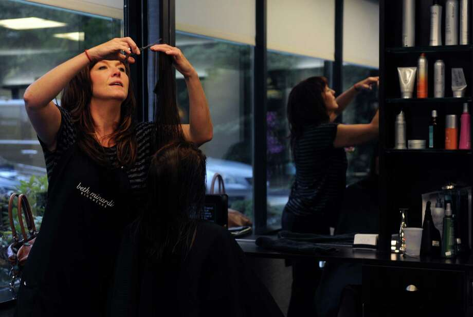 Stylist Karen Whiteley, of Seymour, gives a client a trim at Aqua Salon and Spa, located within Enterprise Corporate Park in Shelton, Conn., Tuesday, Aug. 12, 2014. Ammenities such as this help office complexes lure tenants. Photo: Autumn Driscoll / Connecticut Post