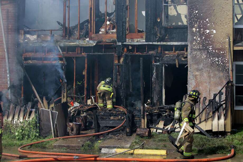 Firefighters work at the scene of a three-alarm fire at the Mar Del Sol Apartments on Tuesday. Photo: Melissa Phillip, Staff / © 2014  Houston Chronicle