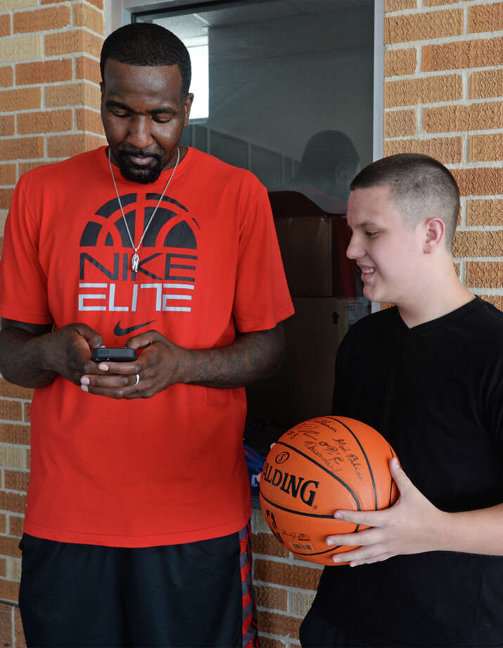 Basketball star Kendrick Perkins programs his cell phone number into William Barton's phone after the two met at Ozen on Tuesday. Barton, who is autistic, was told by Perkins to call so they would have each other's number. Photo taken Tuesday, August 12, 2014 Guiseppe Barranco/@spotnewsshooter Photo: Guiseppe Barranco, Photo Editor