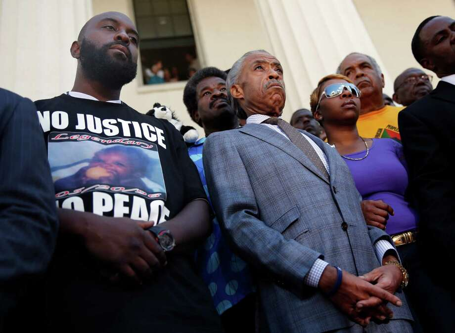 Civil rights leader the Rev. Al Sharpton, center, stands with the parents of Michael Brown - Lesley McSpadden and Michael Brown Sr. - during a news conference outside the Old Courthouse on Tuesday in St. Louis. Photo: Jeff Roberson, STF / AP