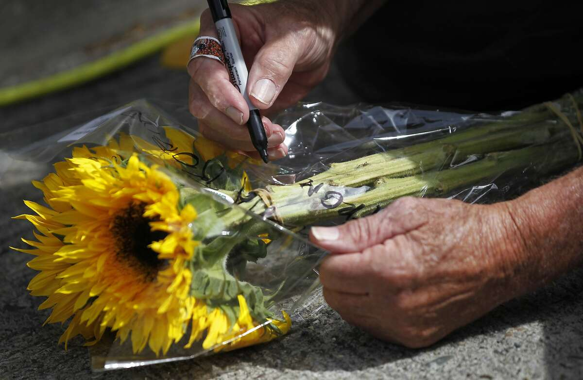 """Danvers Fletcher, 63, of Hawaii, writes a note to Robin Williams before delivering a bouquet of flowers to a temporary shrine for him August 12, 2014 at the home where """"Mrs. Doubtfire"""" was filmed in San Francisco, Calif. Williams was found dead in his home on Monday."""