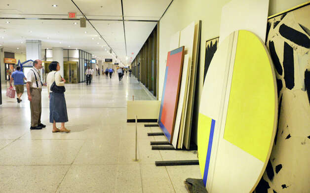 Passers by stop to look at artwork stacked against the walls on the Concourse as portions of the Empire State Plaza Art Collection are reinstalled to different locations on the Concourse and Corning Tower Tuesday August 12, 2014, in Albany, NY.  (John Carl D'Annibale / Times Union) Photo: John Carl D'Annibale, Albany Times Union / 00028130A