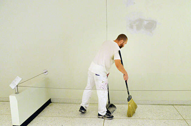 An OGS worker cleans up as the artwork on the Concourse are removed as portions of the Empire State Plaza Art Collection are reinstalled to different locations on the Concourse and Corning Tower Tuesday August 12, 2014, in Albany, NY.  (John Carl D'Annibale / Times Union) Photo: John Carl D'Annibale, Albany Times Union / 00028130A
