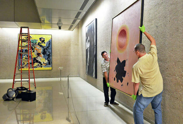 Technicians Harry Klein, left, and Rob Conzett of the Williamstown Art Conservation Center move Adolph Gottlieb's Orange Glow, a 1967 oil on canvas, on the Concourse level of the Corning Tower as portions of the Empire State Plaza Art Collection are reinstalled to different locations on the Concourse and Corning Tower Tuesday August 12, 2014, in Albany, NY.  (John Carl D'Annibale / Times Union) Photo: John Carl D'Annibale, Albany Times Union / 00028130A