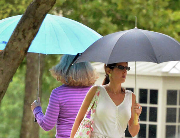 Umbrella-covered pedestrians make their way along Washington Avenue as a light rain begins to fall Tuesday August 12, 2014, in Albany, NY.  (John Carl D'Annibale / Times Union) Photo: John Carl D'Annibale, Albany Times Union