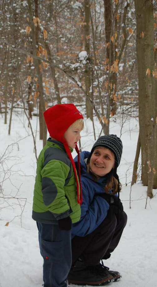 Cari Pfeiffer, of Southport, and her four-year-old son Torin, take a short break during a nature walk at Earthplace on Wednesday. Photo: Anthony Karge / Westport News