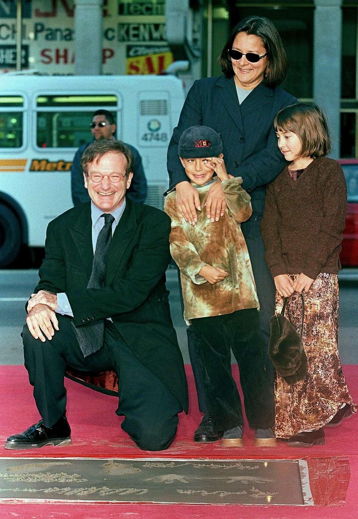 This file photo taken on December 22, 1998 shows US Academy Award-winning actor Robin Williams (left) posing with family members Cody (center), Zelda (right) and wife Marsha (back right) during Williams' hand and footprint ceremony outside the Mann's Chinese Theatre in Hollywood, California. Oscar-winning actor and comedian Robin Williams died on August 11, 2014 after battling depression, triggering an outpouring of tributes to one of the most beloved entertainers of his generation.