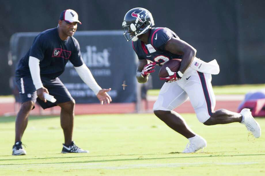 Mostly a spectator the last few years with the Eagles and Chargers, new Texans  running back Ronnie Brown got on the field quickly Tuesday, when he was under the watchful eye of running backs coach Charles London, left. Photo: Brett Coomer, Staff / © 2014 Houston Chronicle