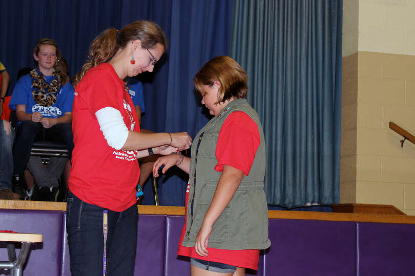 Heather Buskirk ties a red string around the wrist of Rya-Marie Critchley of Northville, a member of