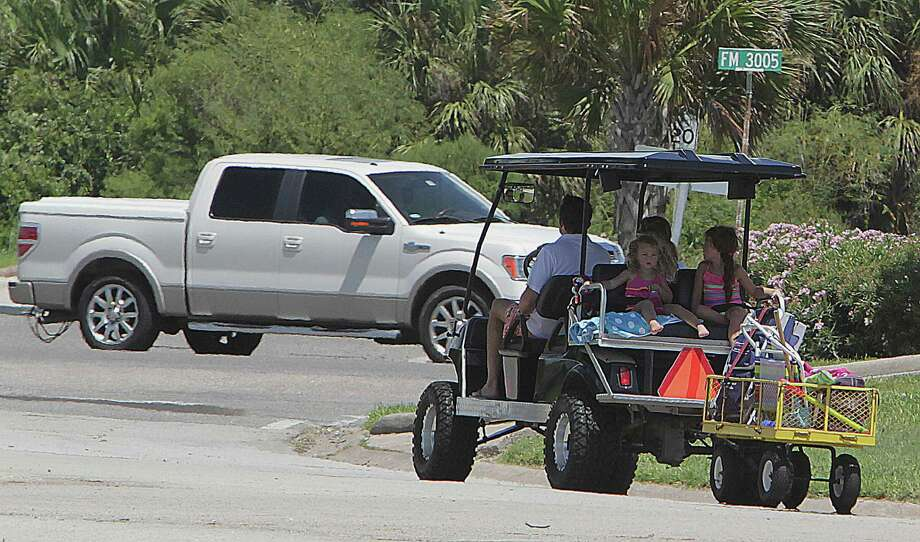 A golf cart with an extra trailer carries a family on a weekend jaunt in the Pirates Beach subdivision last Saturday. Photo: James Nielsen, Staff / © 2014  Houston Chronicle