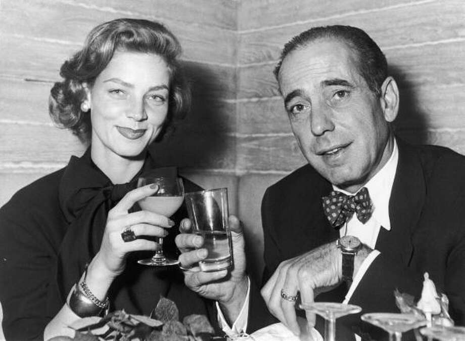 FRANCE - JANUARY 01:  In 1951 the American couple, actors Humphrey BOGART and Lauren BACALL, clink their glasses together at the CALVAVADOS cabaret on the Champs-Elysees in Paris. The two actors starred together in several films, among them the famous CASABLANCA (1942), TO HAVE AND TO HAVE NOT (1944), THE BIG SLEEP (1946) and KEY LARGO (1948).  (Photo by Keystone-France/Gamma-Keystone via Getty Images) Photo: Keystone-France, Gamma-Keystone Via Getty Images / 1951 Keystone-France