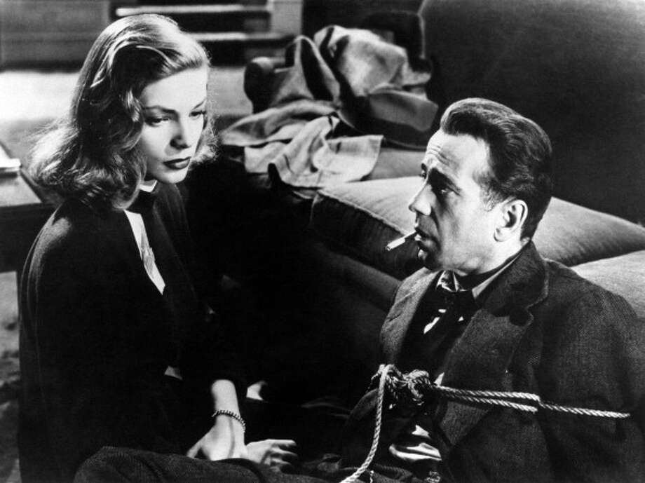American actor Humphrey Bogart tied up with a rope and keeping a cigarette in his mouth looking at his wife, the American actress Lauren Bacall (Betty Jane Perske) in The Big Sleep. 1946. (Photo by Mondadori Portfolio via Getty Images) Photo: Mondadori, Mondadori Via Getty Images / Mondadori Portfolio