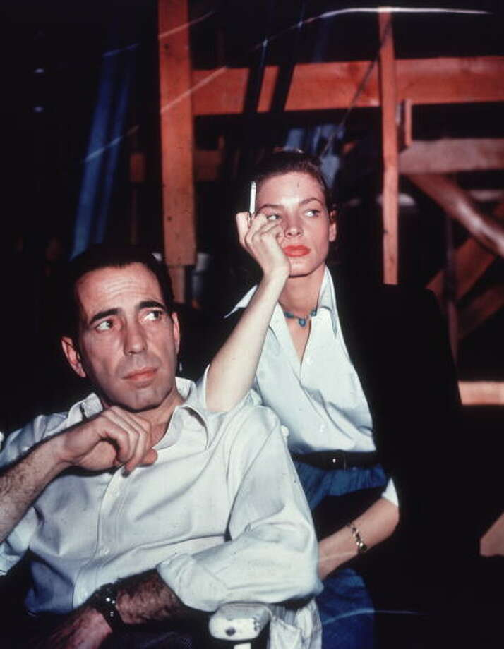 circa 1948:  American actor Lauren Bacall smoking a cigarette and leaning on the shoulder of her husband, actor Humphrey Bogart, on the set of the film 'Key Largo'.  (Photo by Hulton Archive/Getty Images) Photo: Hulton Archive, Getty Images / Archive Photos