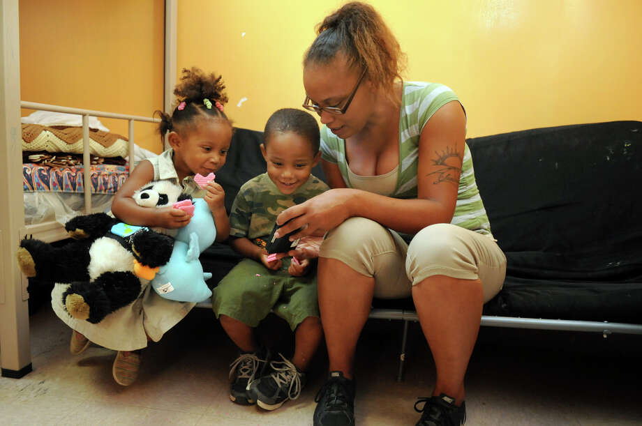 Chrystal McNabney, from right, shares a dancing moment on her cell phone with her children, Bray'Lin, 3, and Isabela Walton, 2, at the Salvation Army shelter in Conroe on Tuesday. Photo: Jerry Baker, Freelance