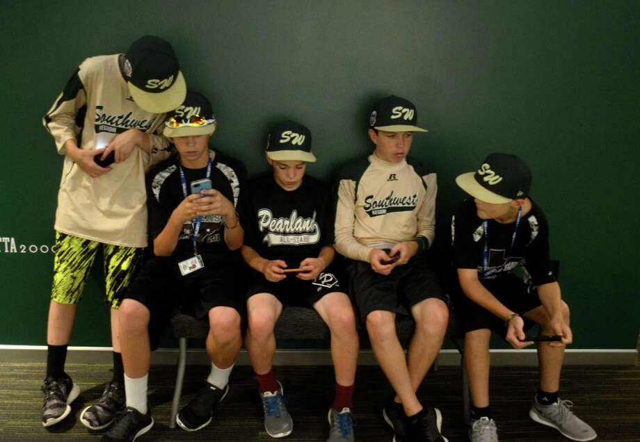 Players from Pearland Little League stop to check their phones during a tour of the World of Little League Museum in Williamsport, Pa on Tuesday, August 12, 2014. From left are, Michael Groover, Mathew Adams, Bryce Laird, Cole Smajstria and Landon Donley. Photo: Ralph Wilson, Chronicle / Houston Chronicle
