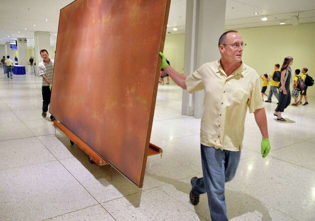 Technicians Harry Klein, left, and Rob Conzett of the Williamstown Art Conservation Center move a large William Pettet acrylic on canvas from 1967 through the Concourse Tuesday, Aug. 12, 2014, in Albany, N.Y. Portions of the Empire State Plaza Art Collection are being reinstalled to different locations on the Concourse and Corning Tower. (John Carl D'Annibale / Times Union) Photo: John Carl D'Annibale / 00028130A