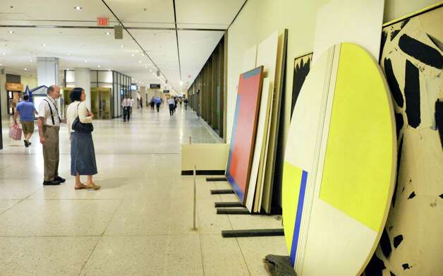 Passers by stop to look at artwork stacked against the walls on the Concourse Tuesday, Aug. 12, 2014, in Albany, N.Y. Portions of the Empire State Plaza Art Collection are being reinstalled to different locations on the Concourse and Corning Tower. (John Carl D'Annibale / Times Union) Photo: John Carl D'Annibale / 00028130A