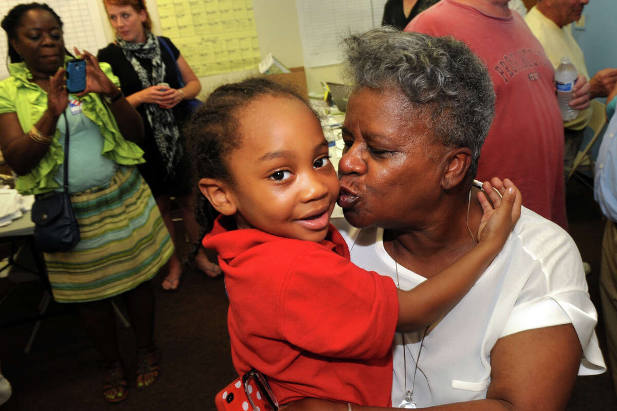 Marilyn Moore kisses her grand-nephew, Malachi Johnson, after her victory over incumbent state Sen. Anthony Musto in Tuesday's Democratic primary in the 22nd District, Aug. 12, 2014.