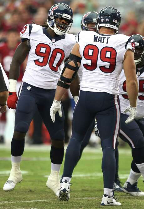 Rookie Jadeveon Clowney, left, and J.J. Watt share one memorable moment Saturday after Watt recorded a first-quarter sack. Photo: Brett Coomer, Staff / © 2014  Houston Chronicle