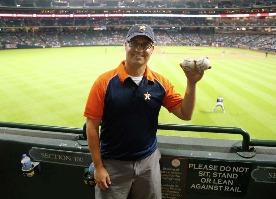 Tim Pinkard of Springfield, Va., was in the right place at the right time - twice - in the Crawford Boxes at Minute Maid Park on Tuesday night, coming up with both of Chris Carter's home run balls in the third and fifth innings. Photo: Karen Warren, Staff / © 2014 Houston Chronicle