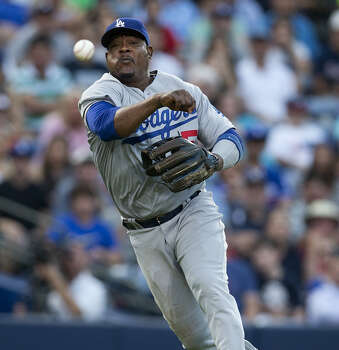 Dodgers third baseman Juan Uribe throws to first but is unable to retire the Braves' Evan Gattis in the second inning in Atlanta. Los Angeles won 4-2. Photo: John Bazemore / Associated Press / AP