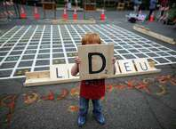 Logan Boetjer, 3, hoists a tile during a Street Scrabble tournament in the First Hill neighborhood. The tournament was organized by the Seattle Department of Transportation to highlight the lack of open space in First Hill and the potential use of street areas as gathering spaces. Photographed on Tuesday, August 12, 2014.