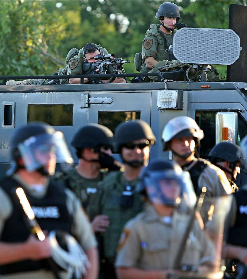 A police sharp shooter keeps an eye on protesters along W. Florissant Avenue on Tuesday, Aug. 12, 2014 near the QuikTrip that was burned down a few days earlier in Ferguson. (AP Photo/St. Louis Post-Dispatch, David Carson) Photo: David Carson, Associated Press