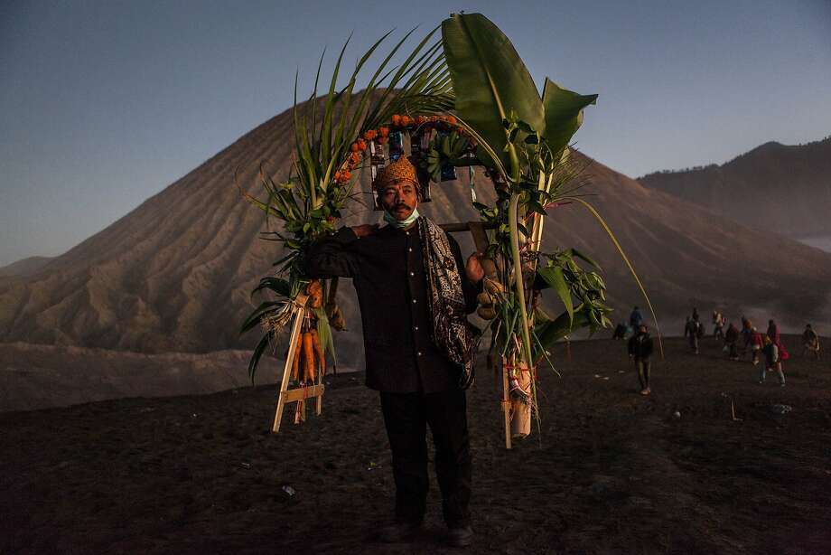 PROBOLINGGO, EAST JAVA, INDONESIA - AUGUST 12:  A Tenggerese worshipper carries vegetables for an offerings during the Yadnya Kasada Festival at crater of Mount Bromo on August 12, 2014 in Probolinggo, East Java, Indonesia. The festival is the main festival of the Tenggerese people and lasts about a month. On the fourteenth day, the Tenggerese make the journey to Mount Bromo to make offerings of rice, fruits, vegetables, flowers and livestock to the mountain gods by throwing them into the volcano's caldera. The origin of the festival lies in the 15th century when a princess named Roro Anteng started the principality of Tengger with her husband Joko Seger, and the childless couple asked the mountain Gods for help in bearing children. The legend says the Gods granted them 24 children but on the provision that the 25th must be tossed into the volcano in sacrifice. The 25th child, Kesuma, was finally sacrificed in this way after initial refusal, and the tradition of throwing sacrifices into the caldera to appease the mountain Gods continues today.  (Photo by Ulet Ifansasti/Getty Images) *** BESTPIX *** Photo: Ulet Ifansasti, Getty Images