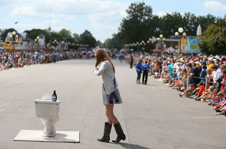 The 2014 Iowa State Fair Queen Elizabeth Glover, of Clay County, watches the outhouse race near the porcelain throne she was tasked with coating in chocolate sauce during the event at the Iowa State Fair on Tuesday, Aug. 12, 2014, in Des Moines, Iowa. (AP Photo/The Des Moines Register, Charlie Litchfield) MAGS OUT, TV OUT, NO SALES, MANDATORY CREDIT Photo: Charlie Litchfield, Associated Press