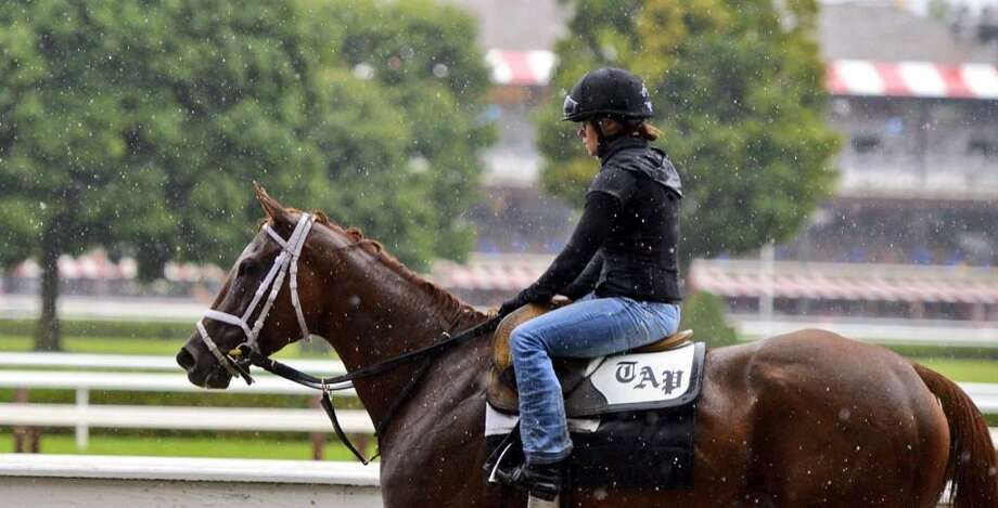 Exercise rider Kali Francois endured the heavy rain Wednesday morning at Saratoga Race Course. (Skip Dickstein / Times Union)