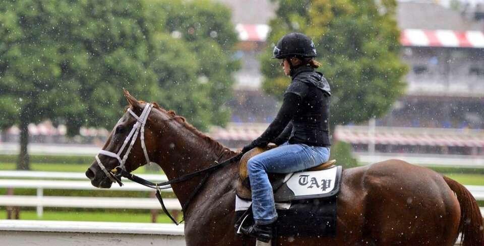 Exercise rider Kali Francois endured the heavy rain Wednesday morning at Saratoga Race Course. (Skip