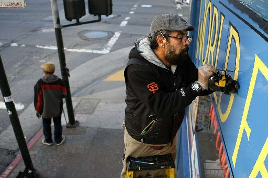 It's been in business since 1947, but is always being upgraded. Painter Wilfredo Leyva works on the sign out front in 2012. Photo: Sean Havey/The Chronicle