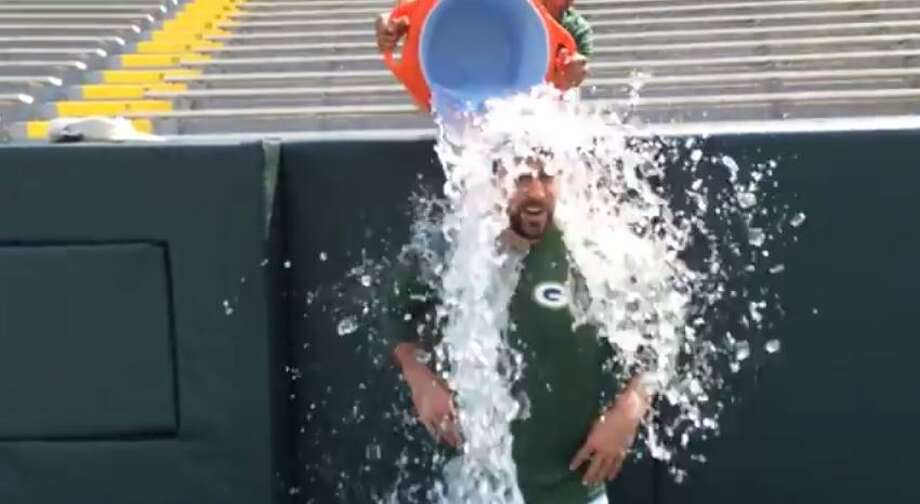 Green Bay Packers quarterback Aaron Rodgers gets splashed with a cooler of ice water on Lambeau Field as part of the ice bucket challenge. Photo: Molina, Maribel, YouTube