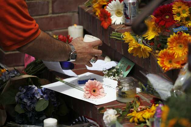 "David Rabb, 45, picks up a candle to light it in front of a temporary shrine for the late Robin Williams August 12, 2014 at the home where ""Mrs. Doubtfire"" was filmed in San Francisco, Calif. Williams was found dead in his home on Monday. Photo: Leah Millis, The Chronicle"