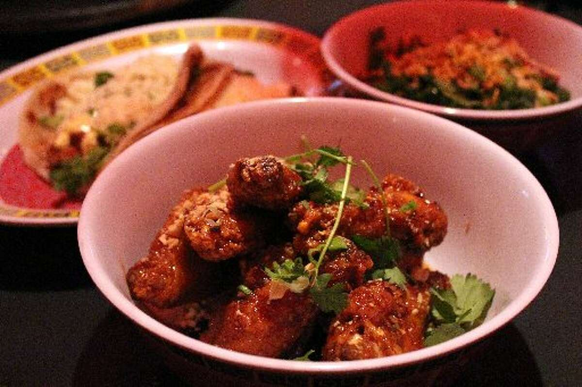 Twice fried chicken wings (center) with crab fat caramel, peanuts and cilantro at Hot Joy.