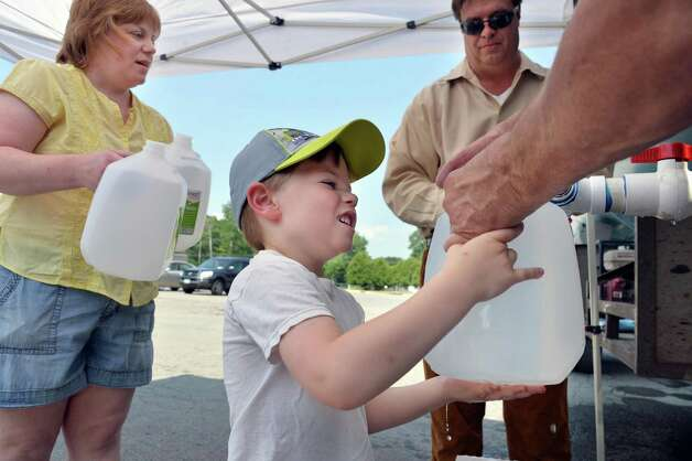 Six-year-old Dominick Brooks helps his mother Denise Brooks, left, fill gallon water bottles with fresh water at a town water station at the former Curry Road Shopping Center Tuesday July 1, 2014, in Rotterdam, NY.  Four water main breaks left more than two-thirds of town residents without water   (John Carl D'Annibale / Times Union) Photo: John Carl D'Annibale / 00027589A