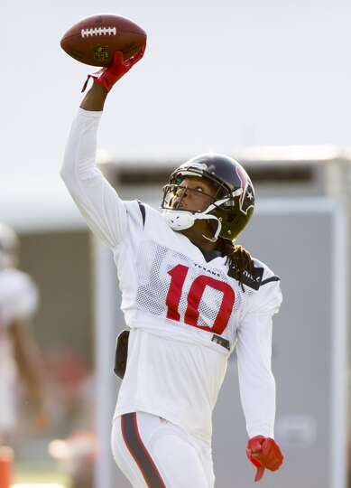 Texans wide receiver DeAndre Hopkins reaches up to catch a football .