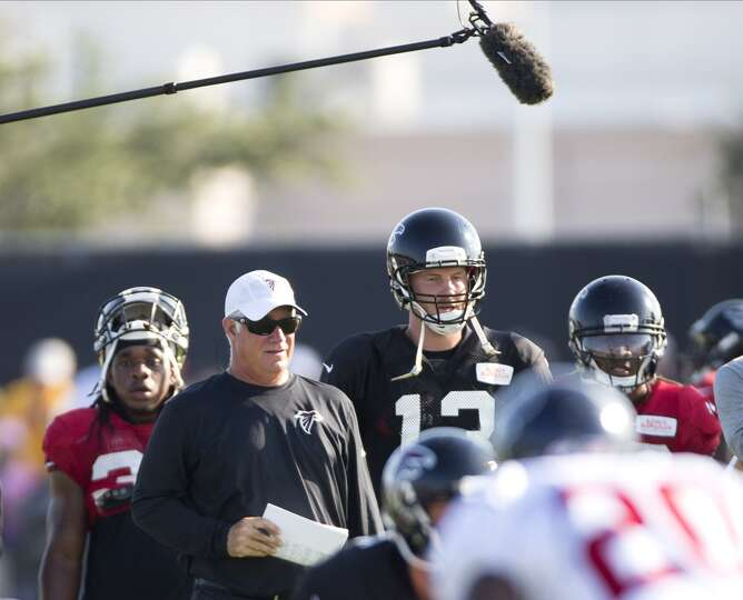 Atlanta Falcons head coach Mike Smith stands next to quarterback T.J. Yates (13) during during a joi