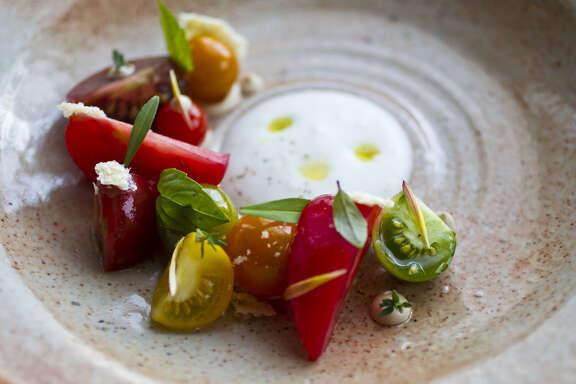Oxheart:  Tomatoes (from Three Sisters Farm) served with bay leaf, pine nut puree, spring herbs with milk foam.