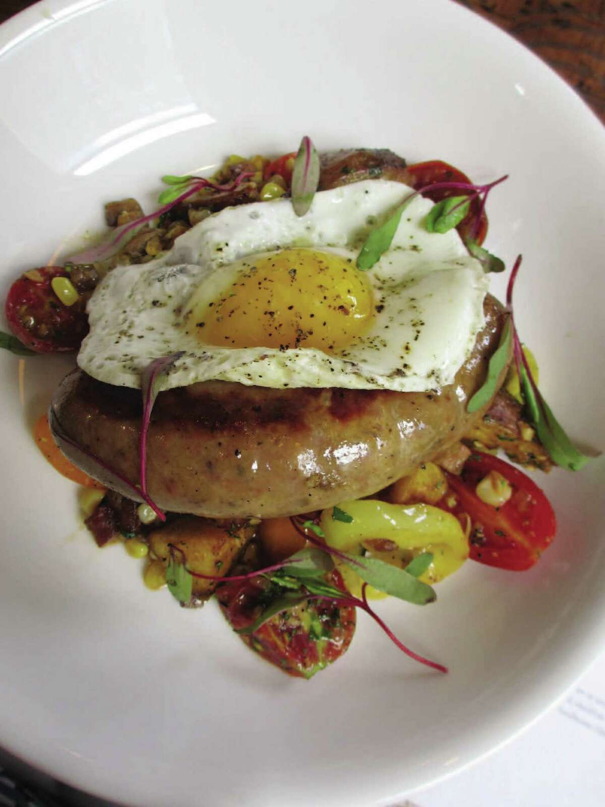 A dish called Wurst Case Scenario (sausage with a fried egg) is served at lunch at Cured, a restaurant in the Pearl that specializes in cured meat.