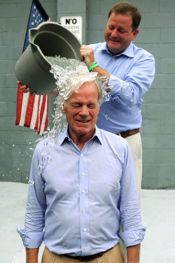 State Sen. John McKinney dumps a bucket of ice on the head of Tom Foley following a press conference in Trumbull, Conn. Aug. 13, 2014. Foley defeated McKinney in TuesdayâÄôs Republican Primary for Governor, and Wednesday accepted McKinneyâÄôs invitation to take the ALS Ice Bucket Challenge. Photo: Ned Gerard / Connecticut Post