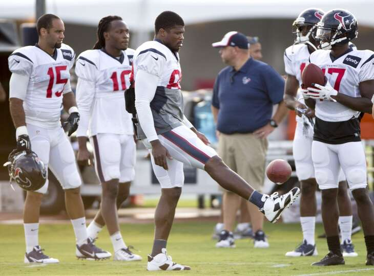 Texans wide receiver Andre Johnson (80) kicks a football in the air.