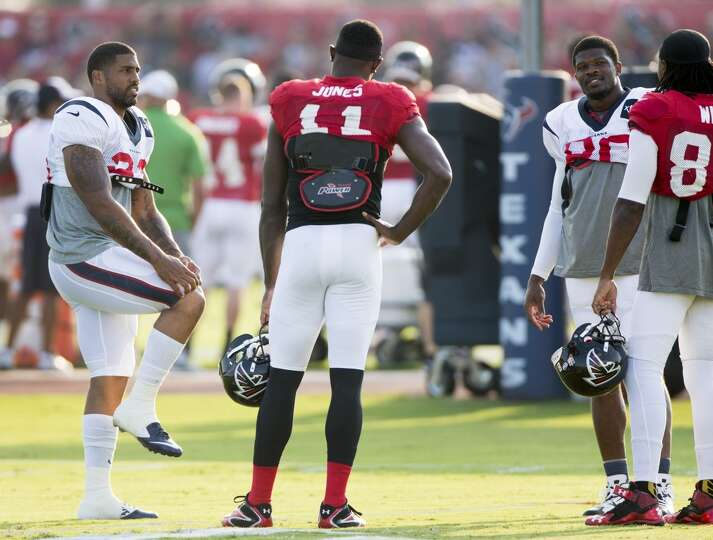 Texans running back Arian Foster (23) and  wide receiver Andre Johnson (80) talk to Atlanta Falcons